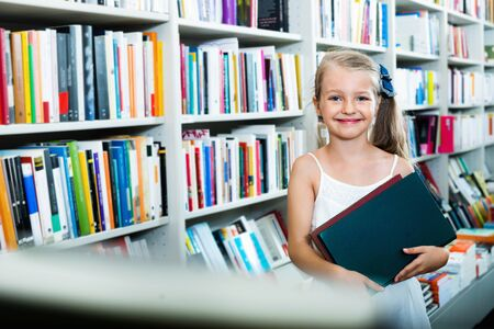 Small smiling blond glad girl standing in book store and taking chosen literature 免版税图像
