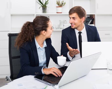 portrait of happy business man and woman colleagues chatting about work in office Foto de archivo