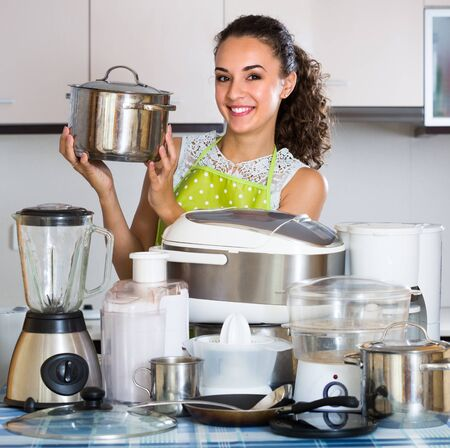 Portrait of positive young brunette woman with kitchen appliances at home