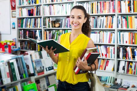 Young woman looking at book in hard cover in bookstore Banco de Imagens