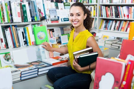 Young smiling female student shopping books in hard cover in bookstore