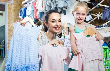 portrait of happy woman and girl shopping kids apparel in clothes store 免版税图像