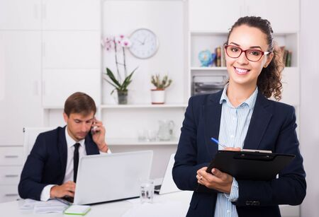 portrait of smiling european business woman holding cardboard in office Stock fotó