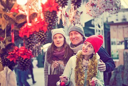 vigorous family of three at Christmas market outdoors