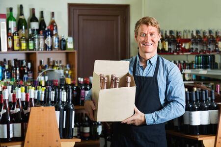 Smiling man seller wearing apron having package box with wine bottles in wine store