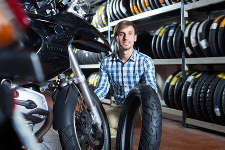 Cliente alegre sosteniendo su motocicleta en el punto de mantenimiento