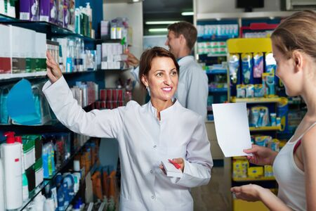 Smiling diligent friendly female pharmacist wearing uniform working in pharmaceutical shop Standard-Bild