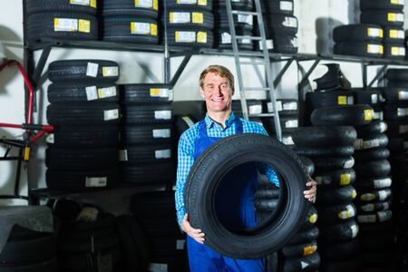 Technician man working with new tyre for car in tire shop Stock Photo