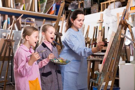 skillful young european woman teacher showing her skills during painting class at art studio