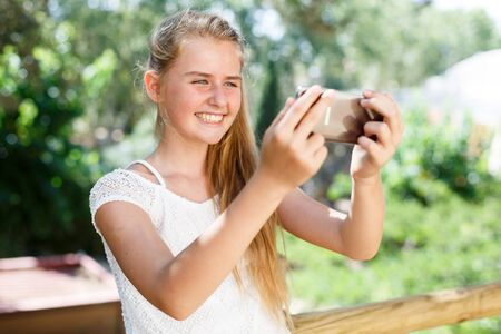 Portrait of  teenage cute girl  making photo with smartphone at sunny day outdoor 写真素材