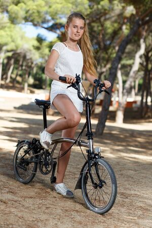Portrait of  teenage girl standing near bicycle ready to go on park ride at summer day