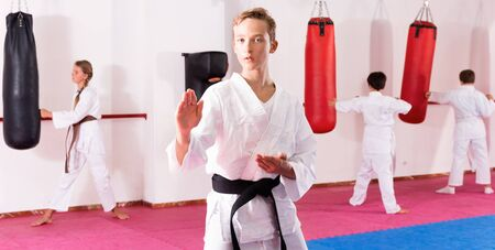 Preteen diligent glad  positive cheerful  boy practicing karate movements with male trainer supervision
