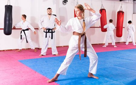 Tween pleasant  girl mastering new taekwondo moves during group class with male coach Banco de Imagens