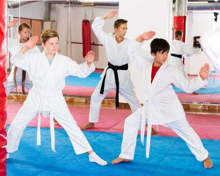attractive kids in kimonos practicing effective karate techniques in group workout at training room