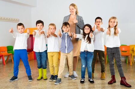 Portrait of happy cheerful positive smiling female teacher with her happy schoolkids in classrom
