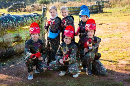 Friendly glad cheerful positive group of children paintball players in camouflage posing with guns on paintball playing field outdoors
