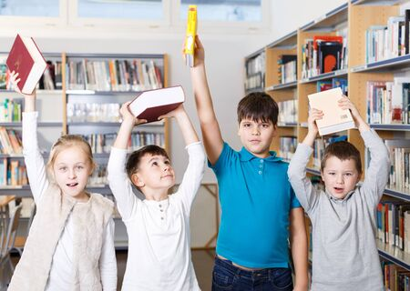 Group portrait of happy children standing with books in hands in modern school library