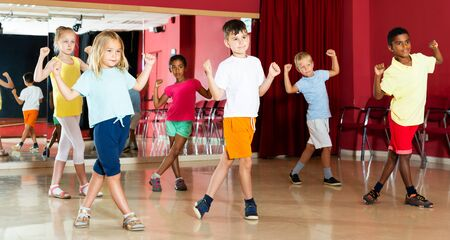 Portrait of group of cheerful little boys and beautiful girls having dancing class  in dance studio
