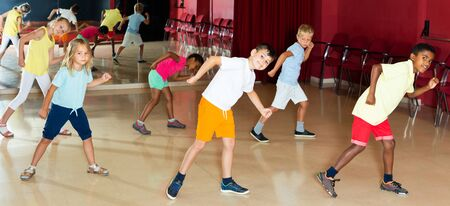Focused children studying modern style dances in dance class indoors Stock Photo