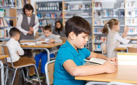 Focused boy reading in school library on background with other students and teacher
