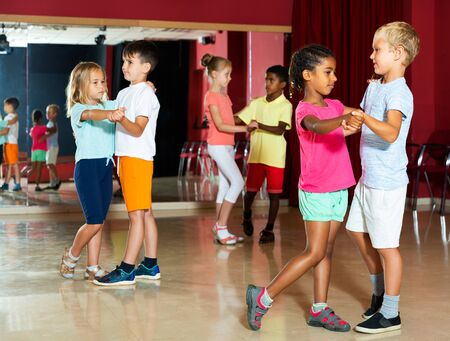 Positive kids primary school trying dancing of partner dance in modern dance studio