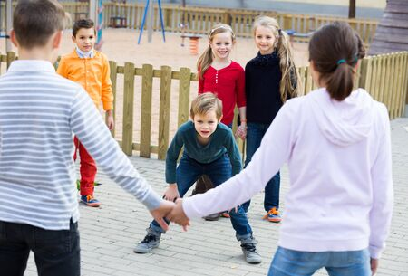 Group of happy glad children playing red rover outdoors