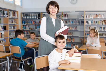 Portrait of smiling female librarian and happy pupil with books in school library