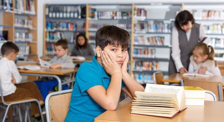 Portrait of upset tween boy reading in school library on background with other students and teacher