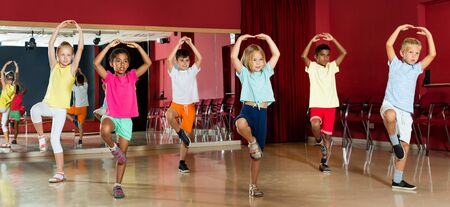 Group of positive childrens trying balance movements of ballet at classroom