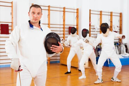 Active young glad cheerful  smiling male fencer in uniform standing with mask and foil at fencing room