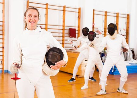 Positive active young female fencer standing at the fencing workout