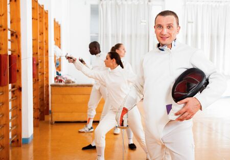Active glad cheerful  smiling male fencer in uniform standing with mask and foil at fencing room
