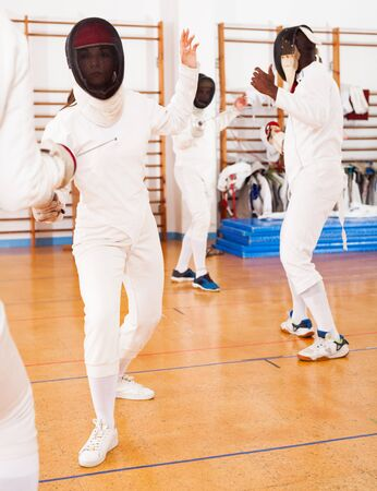 Sporty young active woman fencer practicing fencing combination in training room