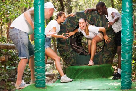 Group of excited people passing obstacles at adventure park Stock Photo