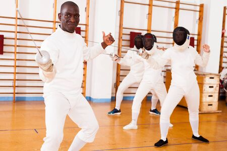Sporty african american man fencer practicing effective fencing techniques in training room