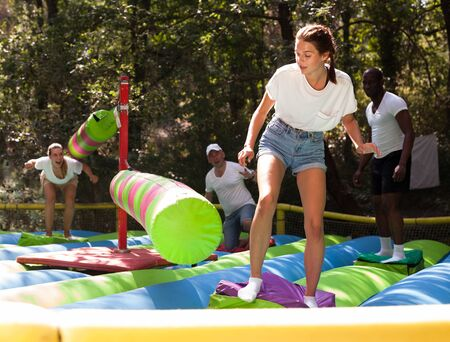Team of friends having fun on an inflatable trampoline in an attraction park