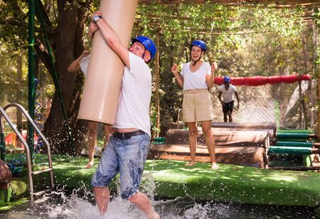 Group of excited people passing water obstacle course at adventure park