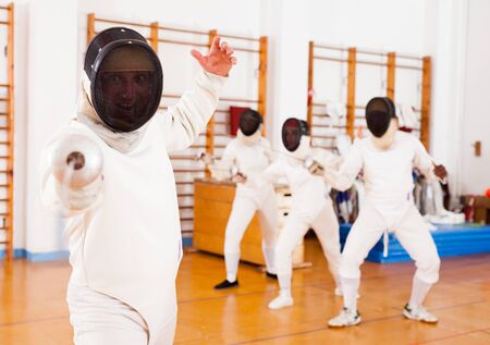 Sporty young man fencer practicing effective fencing techniques in training room