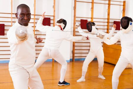 Sporty african american man fencer practicing effective fencing techniques at a training room