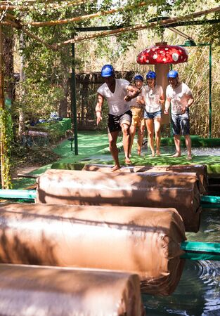 Two teams compete on an obstacle course in an amusement park.