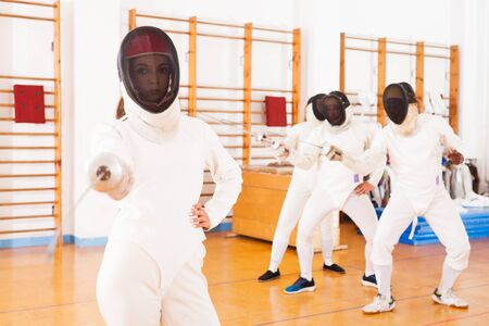 active woman fencer practicing fencing combination in training room