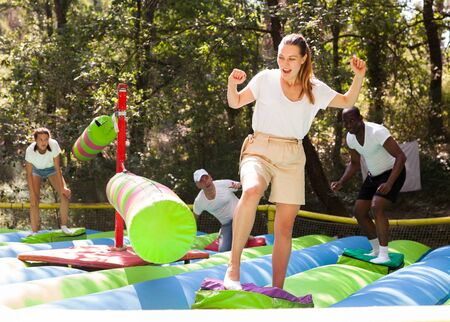 Funny adult friends are jumping on an inflatable trampoline