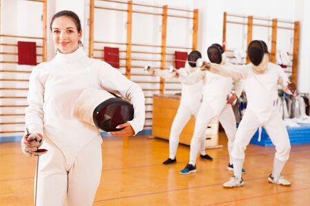 Positive active young female fencer standing at fencing workout Stock Photo