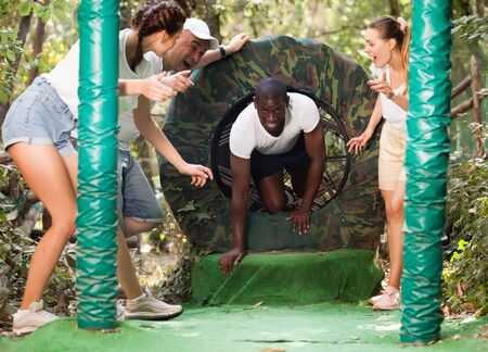 Group of enthusiastic men and women passing obstacles and having fun at adventure park