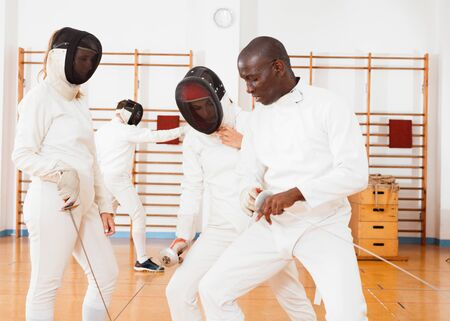 Glad cheerful  smiling woman fencer practicing new movements with trainer  at fencing room