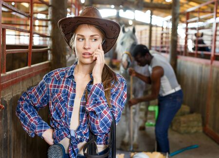 Young woman farmer worker using her mobile phone in stable