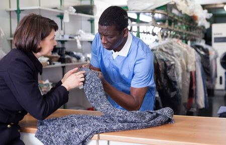 Gerente de lavandería trabajando con cliente mujer, recibiendo ropa para tintorería