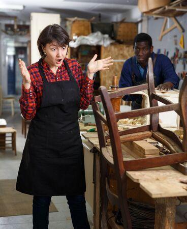 Outraged woman restorer standing near vintage armchair at workshop
