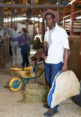 Farm workers man and woman preparing horse harness at stable Stock Photo
