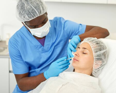 Portrait of woman client and doctor during beauty facial injections in medical esthetic office